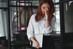 Τονισμένη ασιατική επιχειρησιακή γυναίκα που στέκεται και που αισθάνεται απογοητευμένο ή κουρασμένο στην αρχή Στοκ Φωτογραφίες