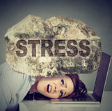 Τονισμένη γυναίκα με το κεφάλι που συμπιέζεται μεταξύ του lap-top και ενός βράχου Στοκ φωτογραφία με δικαίωμα ελεύθερης χρήσης