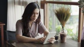 Τονισμένη γυναίκα που έχει το πρόβλημα πιστωτικών καρτών να ψωνίσει on-line με την ταμπλέτα στο café απόθεμα βίντεο