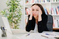 Τονισμένη γυναίκα που αισθάνεται τον πονοκέφαλο στην εργασία στοκ εικόνες με δικαίωμα ελεύθερης χρήσης