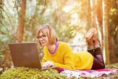Τονισμένη εικόνα ενός πορτρέτου κοριτσιών freelancer σε ένα κίτρινο πουλόβερ και τα γυαλιά που εξετάζουν σκεπτικά την οθόνη lap-t Στοκ Εικόνες