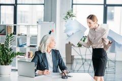 Τονισμένη επιχειρηματίας με τα έγγραφα που υποστηρίζει στη συνεδρίαση συναδέλφων στον εργασιακό χώρο στην αρχή Στοκ φωτογραφία με δικαίωμα ελεύθερης χρήσης