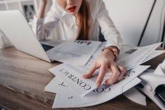 Τονισμένη επιχειρηματίας με τα έγγραφα lap-top και συμβάσεων που κάθεται στον πίνακα στην αρχή Στοκ Φωτογραφία
