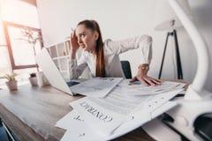 Τονισμένη επιχειρηματίας με τα έγγραφα lap-top και συμβάσεων που κάθεται στον πίνακα στην αρχή Στοκ Φωτογραφίες