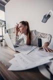 Τονισμένη επιχειρηματίας με τα έγγραφα lap-top και συμβάσεων που κάθεται στον πίνακα στην αρχή Στοκ Εικόνες