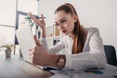 Τονισμένη επιχειρηματίας με το lap-top και έγγραφα που κάθονται στον πίνακα στην αρχή Στοκ εικόνα με δικαίωμα ελεύθερης χρήσης