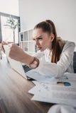 Τονισμένη επιχειρηματίας με το lap-top και έγγραφα που κάθονται στον πίνακα στην αρχή Στοκ Εικόνες