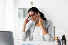 Τονισμένη επιχειρηματίας με το smartphone στο γραφείο Στοκ Εικόνες