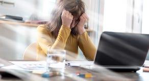 Τονισμένη επιχειρηματίας που κάθεται την επίδραση στην αρχή, ελαφριών ακτίνων Στοκ φωτογραφία με δικαίωμα ελεύθερης χρήσης