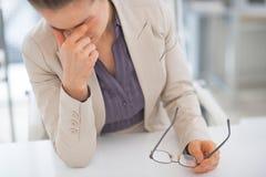 Τονισμένη επιχειρησιακή γυναίκα με eyeglasses στην αρχή Στοκ φωτογραφία με δικαίωμα ελεύθερης χρήσης