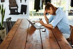 Τονισμένη επιχειρησιακή γυναίκα που εργάζεται στο φορητό προσωπικό υπολογιστή Πόνος πονοκέφαλου στοκ εικόνα με δικαίωμα ελεύθερης χρήσης