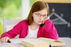 Τονισμένη και κουρασμένη μαθήτρια που μελετά με έναν σωρό των βιβλίων στο γραφείο της Στοκ Εικόνα