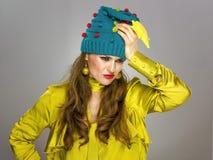 Τονισμένη μοντέρνη γυναίκα καπέλο Χριστουγέννων που απομονώνεται στο αστείο στο γκρι Στοκ Φωτογραφίες