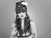 Τονισμένη μοντέρνη γυναίκα στο αστείο καπέλο Χριστουγέννων στο γκρι Στοκ Εικόνες