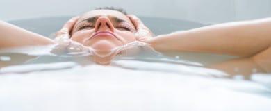 Τονισμένη νέα γυναίκα που βάζει στην μπανιέρα Στοκ Εικόνα