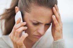 Τονισμένη νέα γυναίκα στο πουλόβερ στο ομιλούν τηλέφωνο κυττάρων παραλιών Στοκ Φωτογραφία