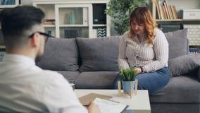 Τονισμένη παχύσαρκη γυναίκα που μοιράζεται τα προβλήματα με τον ψυχοθεραπευτή στην αρχή στην κλινική απόθεμα βίντεο