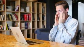 τονισμένη συνεδρίαση επιχειρηματιών στο γραφείο του που χρησιμοποιεί το lap-top απόθεμα βίντεο