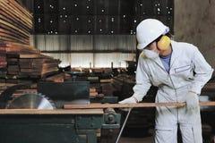 τονισμένη τρύγος εικόνα Ο επαγγελματικός νέος ξυλουργός με τον εξοπλισμό ασφάλειας που κόβει ένα κομμάτι του ξύλου στον πίνακα εί Στοκ Φωτογραφία