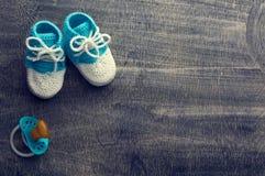 Τονισμένη φωτογραφία των μπλε πλεγμένων bootees παιδιών με λίγη θηλή ο στοκ φωτογραφία με δικαίωμα ελεύθερης χρήσης