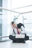 Τονισμένος έξω επιχειρηματίας που κάθεται στο πάτωμα που λειτουργεί στο lap-top Στοκ Φωτογραφία