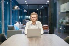 Τονισμένος δυτικός επιχειρηματίας που χρησιμοποιεί ένα lap-top στο καθιστικό στο Νι Στοκ εικόνα με δικαίωμα ελεύθερης χρήσης
