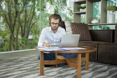 Τονισμένος δυτικός επιχειρηματίας που χρησιμοποιεί ένα lap-top στο καθιστικό Στοκ εικόνα με δικαίωμα ελεύθερης χρήσης