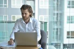 Τονισμένος δυτικός επιχειρηματίας που χρησιμοποιεί ένα lap-top στο καθιστικό Στοκ Φωτογραφίες