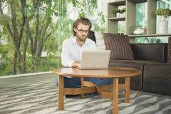 Τονισμένος δυτικός επιχειρηματίας που χρησιμοποιεί ένα lap-top στο καθιστικό Στοκ Εικόνα