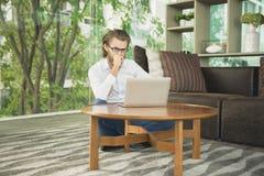 Τονισμένος δυτικός επιχειρηματίας που χρησιμοποιεί ένα lap-top στο καθιστικό Στοκ εικόνες με δικαίωμα ελεύθερης χρήσης