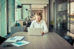 Τονισμένος δυτικός επιχειρηματίας που χρησιμοποιεί ένα lap-top στο καθιστικό Στοκ Φωτογραφία