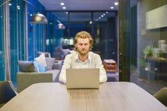 Τονισμένος δυτικός επιχειρηματίας που χρησιμοποιεί ένα lap-top στο καθιστικό στο Νι Στοκ Εικόνες