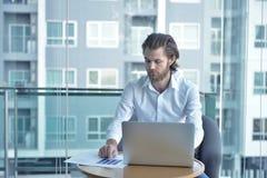 Τονισμένος δυτικός επιχειρηματίας που χρησιμοποιεί ένα lap-top στο καθιστικό Στοκ Εικόνες