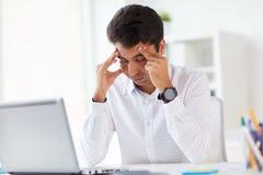 Τονισμένος επιχειρηματίας με το lap-top στο γραφείο Στοκ Φωτογραφίες