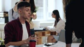 Τονισμένος νέος όμορφος ευρωπαϊκός αρσενικός Διευθυντής επιχείρησης που μιλά στο θηλυκό προϊστάμενο στο σύγχρονο ελαφρύ επιτραπέζ φιλμ μικρού μήκους