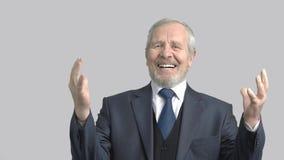 Τονισμένος παλαιότερος επιχειρηματίας, γκρίζο υπόβαθρο απόθεμα βίντεο