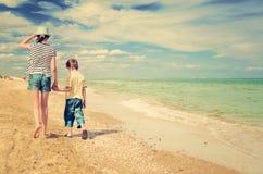 Τονισμένος περίπατος παιδιών εικόνας κατά μήκος της ακτής Στοκ Φωτογραφία