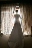 Τονισμένος πυροβολισμός της κομψής νύφης που εξετάζει έξω παράθυρο το ξενοδοχείο Στοκ φωτογραφία με δικαίωμα ελεύθερης χρήσης