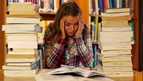 Τονισμένος σπουδαστής που μελετά και που παίρνει τις σημειώσεις στη βιβλιοθήκη που περιβάλλεται από τα βιβλία απόθεμα βίντεο