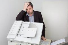 Τονισμένο άτομο που χρησιμοποιεί μια μηχανή αντιγράφων Στοκ Εικόνες