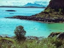 Τονισμένο μόνο άτομο εικόνας που επιπλέει στη νορβηγική θάλασσα μέσω των νησιών Lofoten ενάντια στο σκηνικό των βουνών και του ου Στοκ φωτογραφίες με δικαίωμα ελεύθερης χρήσης