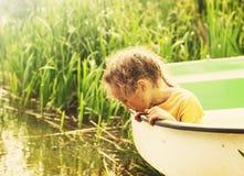 Τονισμένο πορτρέτο λίγης χαριτωμένης συνεδρίασης κοριτσιών στη βάρκα από έναν ποταμό τη θερινή ημέρα Στοκ Εικόνες