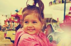 Τονισμένο πορτρέτο του ευτυχούς χαριτωμένου χαμογελώντας κοριτσιού που οδηγά στο ιπποδρόμιο στοκ εικόνες