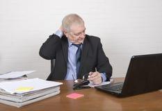 Τονισμένο ώριμο άτομο στην εργασία που εξετάζει τη γραφική εργασία Στοκ εικόνες με δικαίωμα ελεύθερης χρήσης