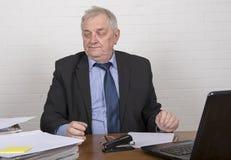 Τονισμένο ώριμο άτομο στην εργασία που εξετάζει τη γραφική εργασία Στοκ Φωτογραφίες