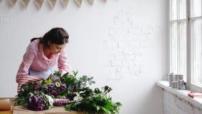 Τον ανθοκόμο που τελειώνουν δημιουργεί μια όμορφη ανθοδέσμη των μεγάλων λουλουδιών απόθεμα βίντεο
