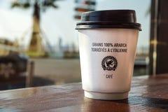 Τον Αύγουστο του 2017 της Νίκαιας, Γαλλία -02: Φλυτζάνι καφέ εγγράφου από τη καφετερία στο ξύλινο υπόβαθρο Στοκ Φωτογραφία