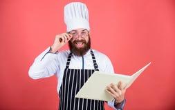 Τον ερασιτέχνη μάγειρα που διαβάζεται τις συνταγές βιβλίων Το άτομο μαθαίνει τη συνταγή Δοκιμάστε κάτι νέο Μαγειρική στο μυαλό μο στοκ φωτογραφία