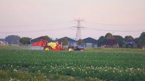 Τον Ιούλιο του 2018 circa του Ρότερνταμ, Κάτω Χώρες: Άρδευση ενός τομέα πατατών με ένα τρακτέρ απόθεμα βίντεο