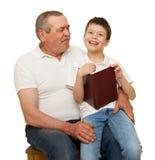 Τον παππού και τα εγγόνια που διαβάζονται το βιβλίο Στοκ Εικόνα